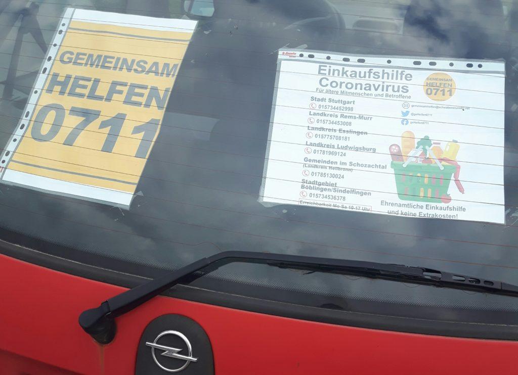 """Das Bild zeigt einen roten Opel Corsa auf dessen Heckscheibe zwei Flyer Kleben. """"Gemeinsam helfen 0711"""" und """"Einkaufshilfe Coronavirus"""". Während der Corona-Krise kaufen VfB-Fußball-Ultras für Senioren ein."""
