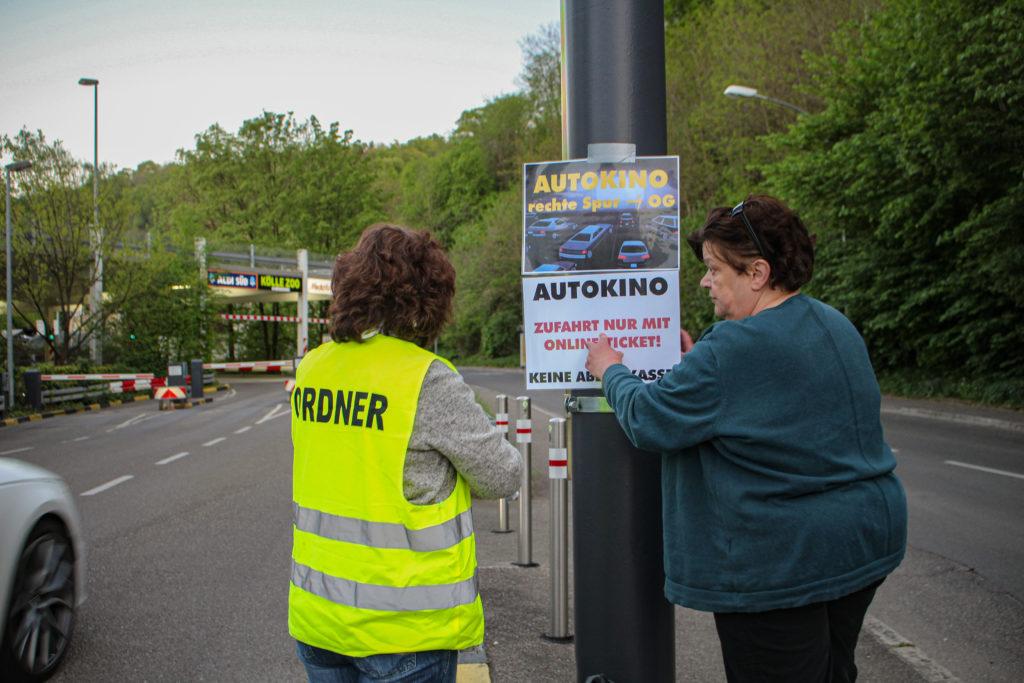 Sibylle Tejkl und eine ehrenamtliche Helferin kleben einen Flyer vor den Eingang des Autokinos.