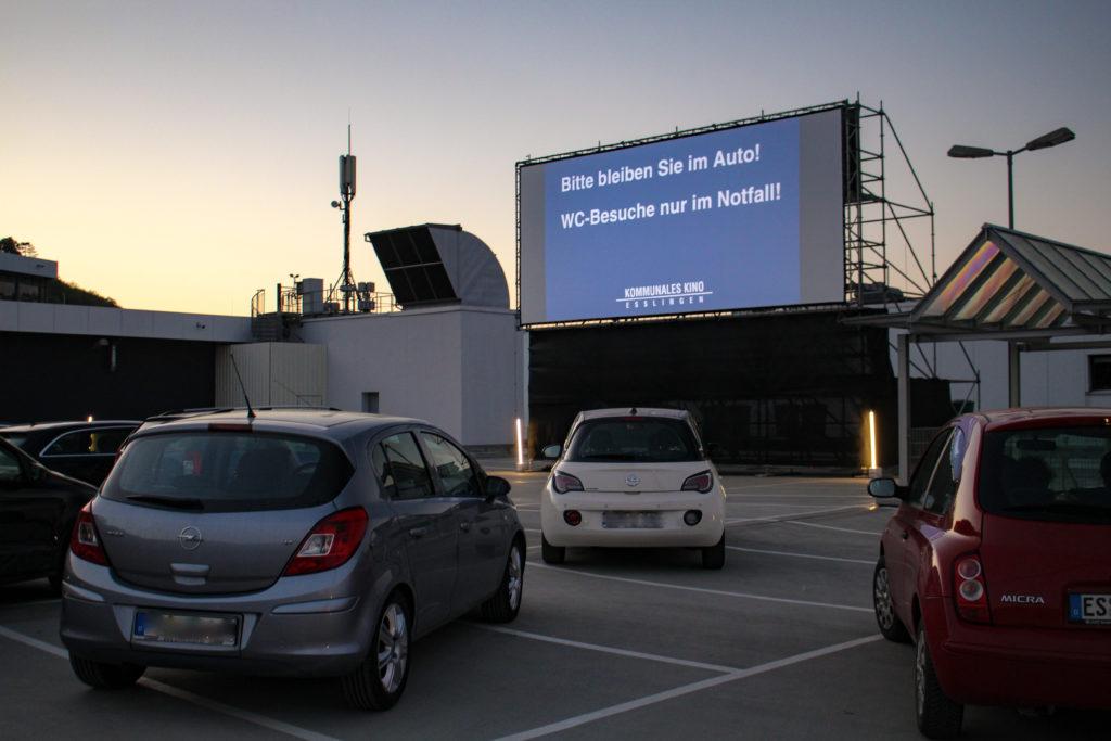 Kinoleinwand zeigt den Schriftzug: Bitte bleiben Sie im Auto! WC-Besuche nur im Notfall.
