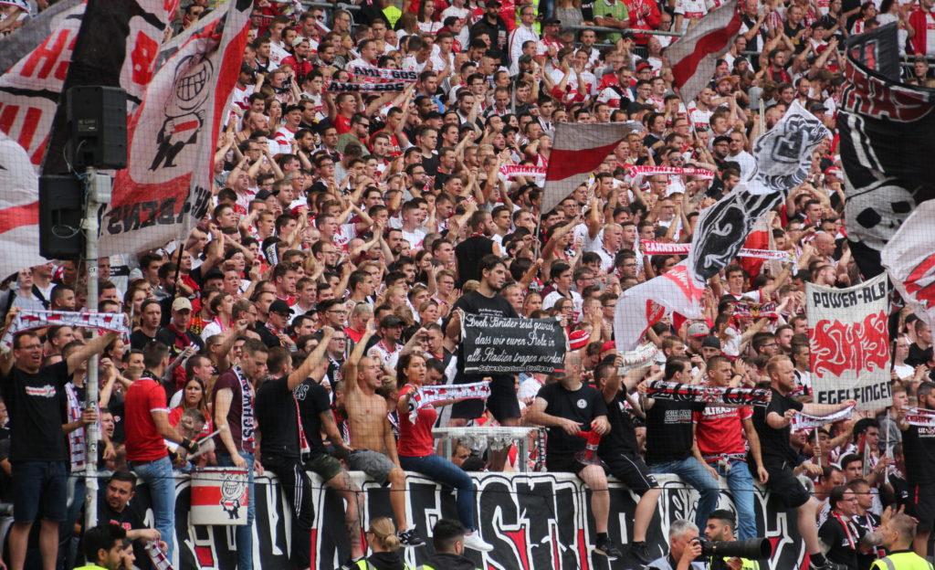 Schwabensturm Fußball-Ultras schenken im Stadion weiß-rote Fahnen und feuern ihre Mannschaft, den VfB, ein.