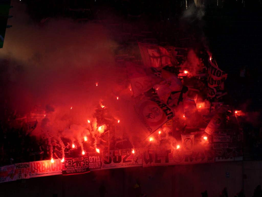 Schwabensturm Fußball-Ultras zünden im Stadion rot leuchtende Pyrotechnik und schwenken Fahnen. Ansonsten ist es dunkel, um sie herum.