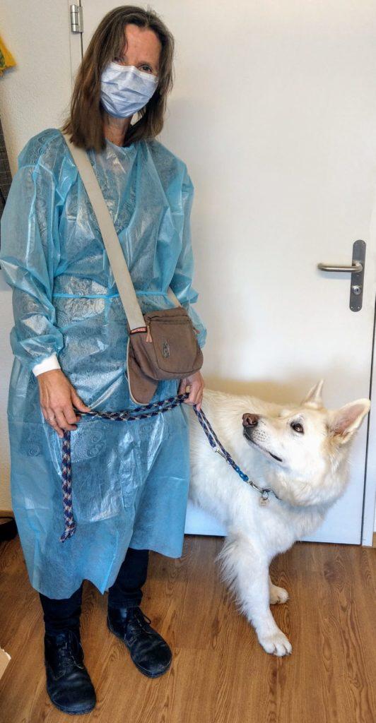 Seelsorge mit Schutzanzug, Schutzmaske und Therapiehund